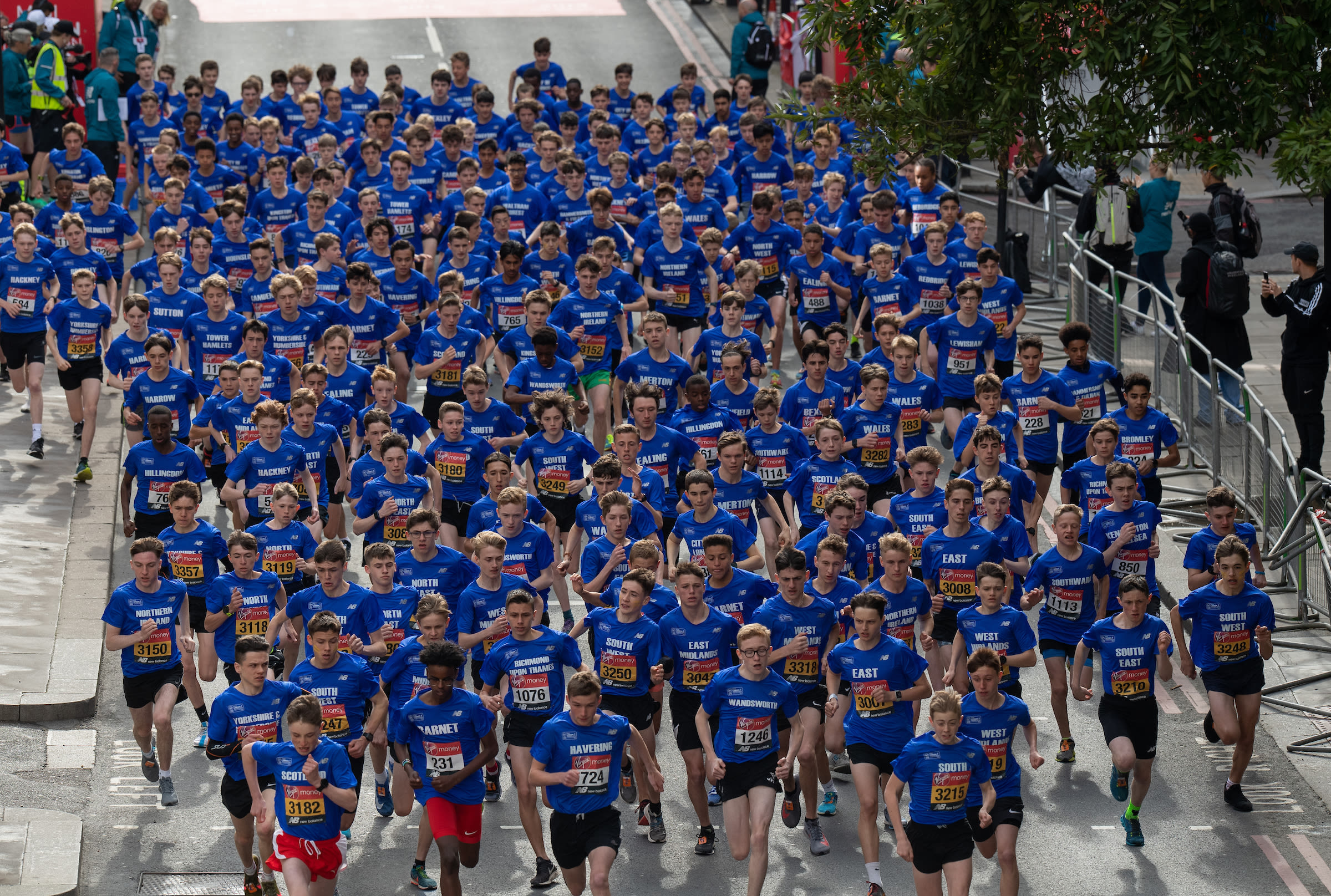 A crowd of school boys wearing blue t-shirts run in the Virgin Money Giving Mini London Marathon 2019