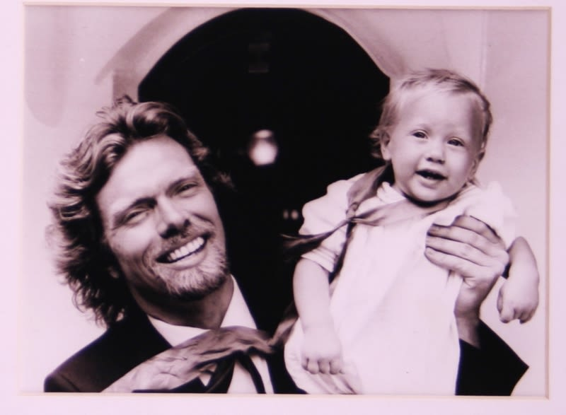 Black and white picture of Richard Branson holding up Sam Branson as a baby and smiling
