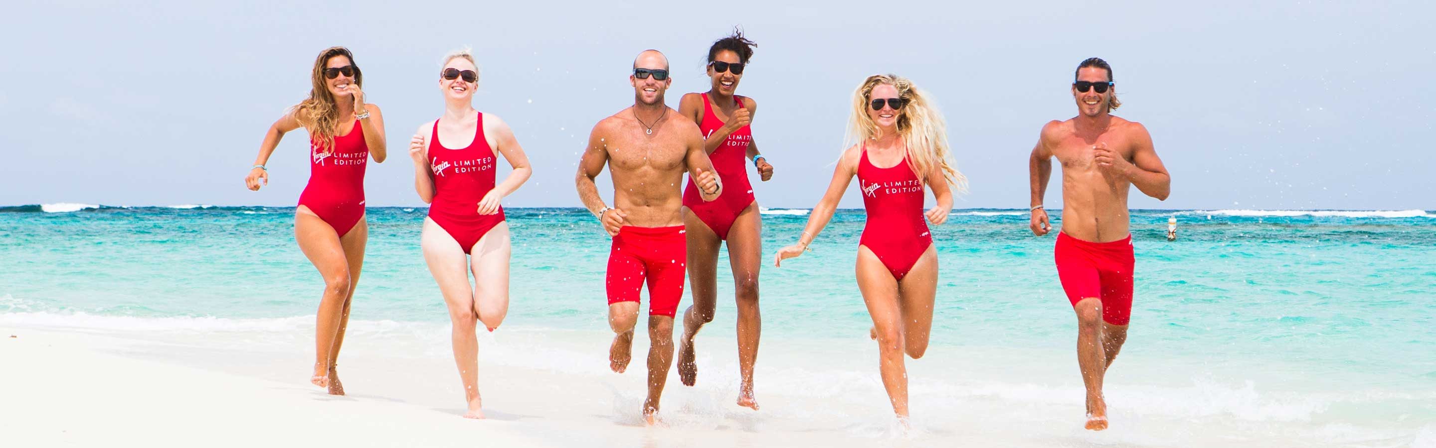 Five people wearing red swimsuits or swim shorts run on a white sandy beach