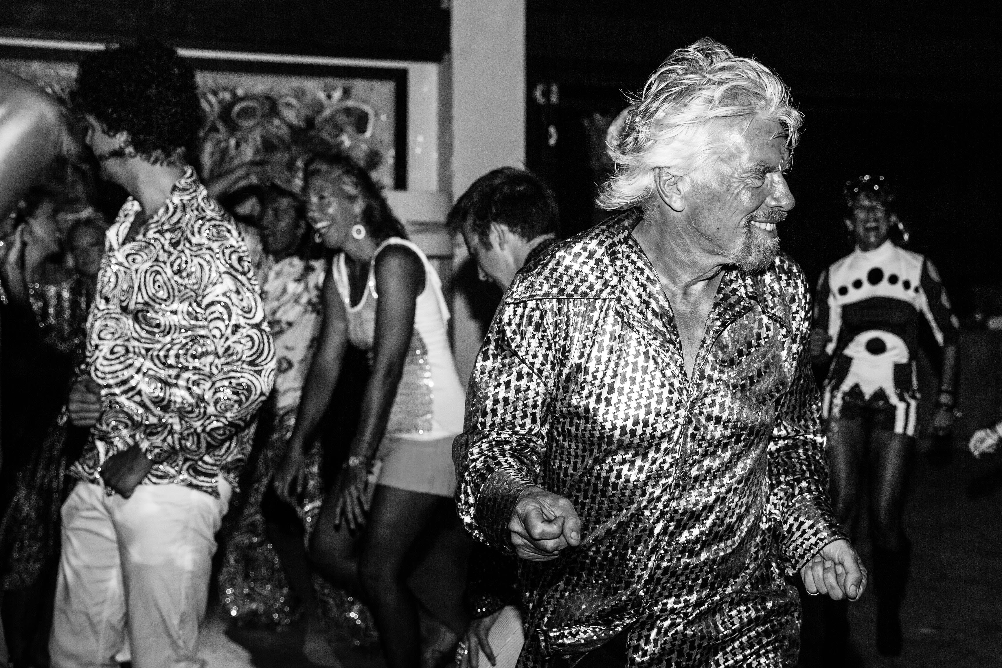 Black and white photo of Richard Branson dancing in snazzy shirt