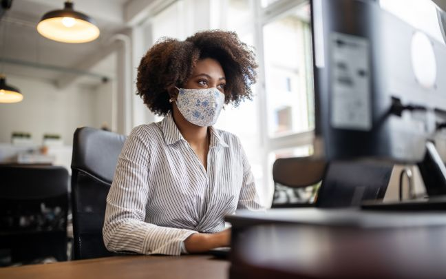 A woman wears a face mask while in her office