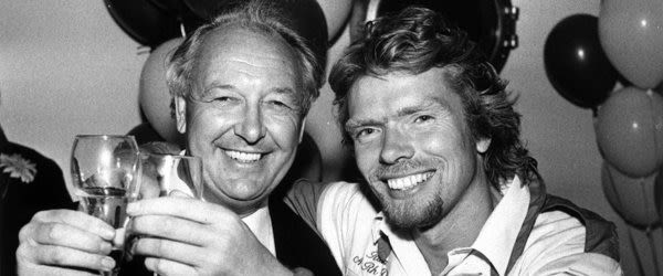 Black and white photo of Richard Branson and Freddie Laker raising glasses and smiling