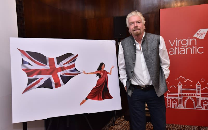 Richard Branson stands next to an illustration of Virgin Atlantic's new Flying Icon of an Indian woman