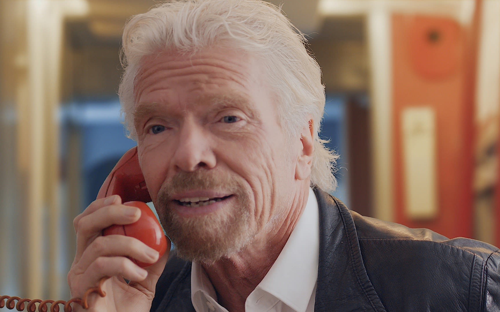 Richard Branson takes a call on a red phone for Virgin Trains