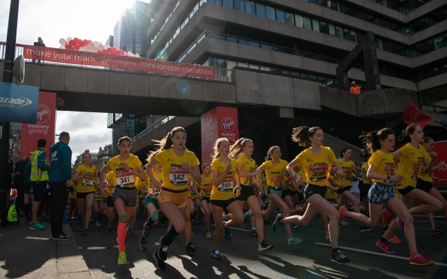 School children wearing yellow t-shirts run in the Virgin Money Giving Mini London Marathon 2019