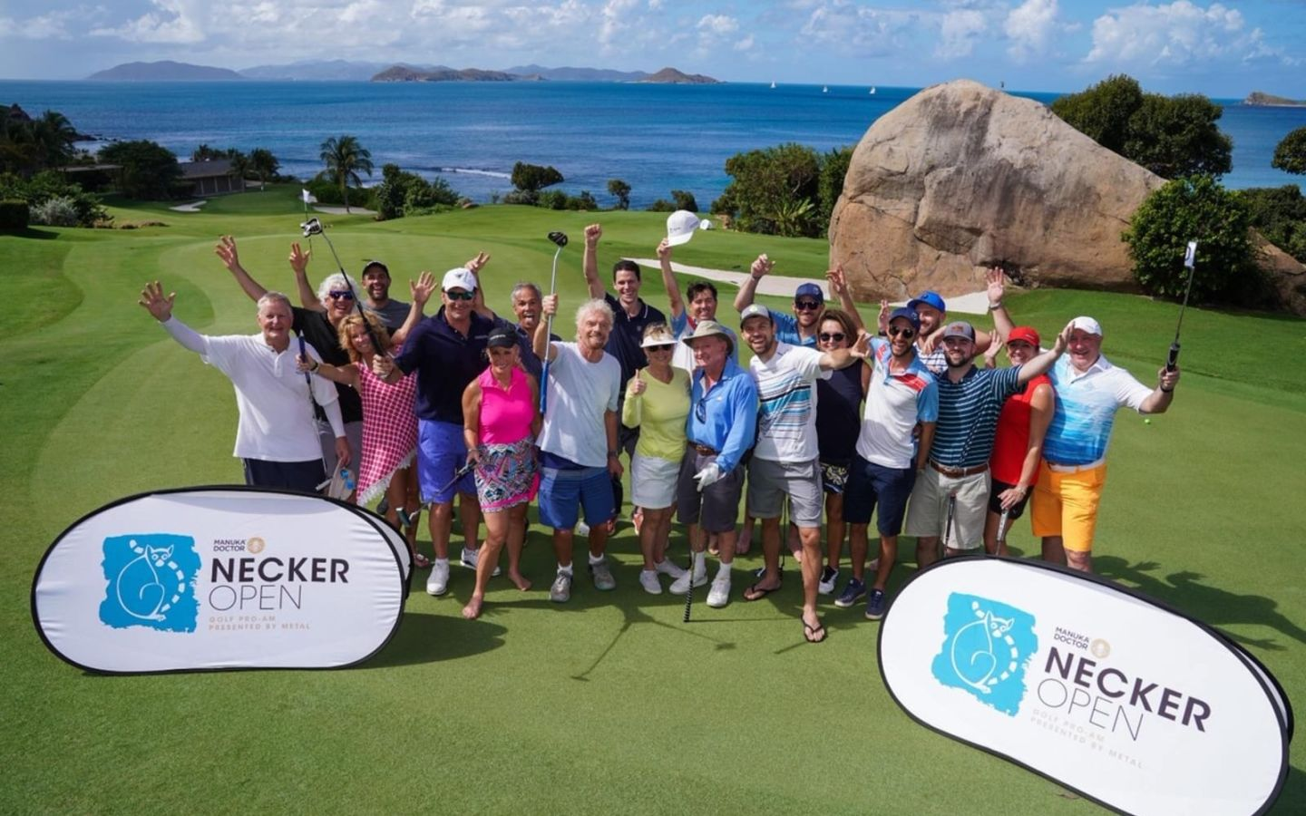 Richard Branson stands with a group of golfers at the Necker Open.  It's a sunny day and the sea is visible in the distance behind them