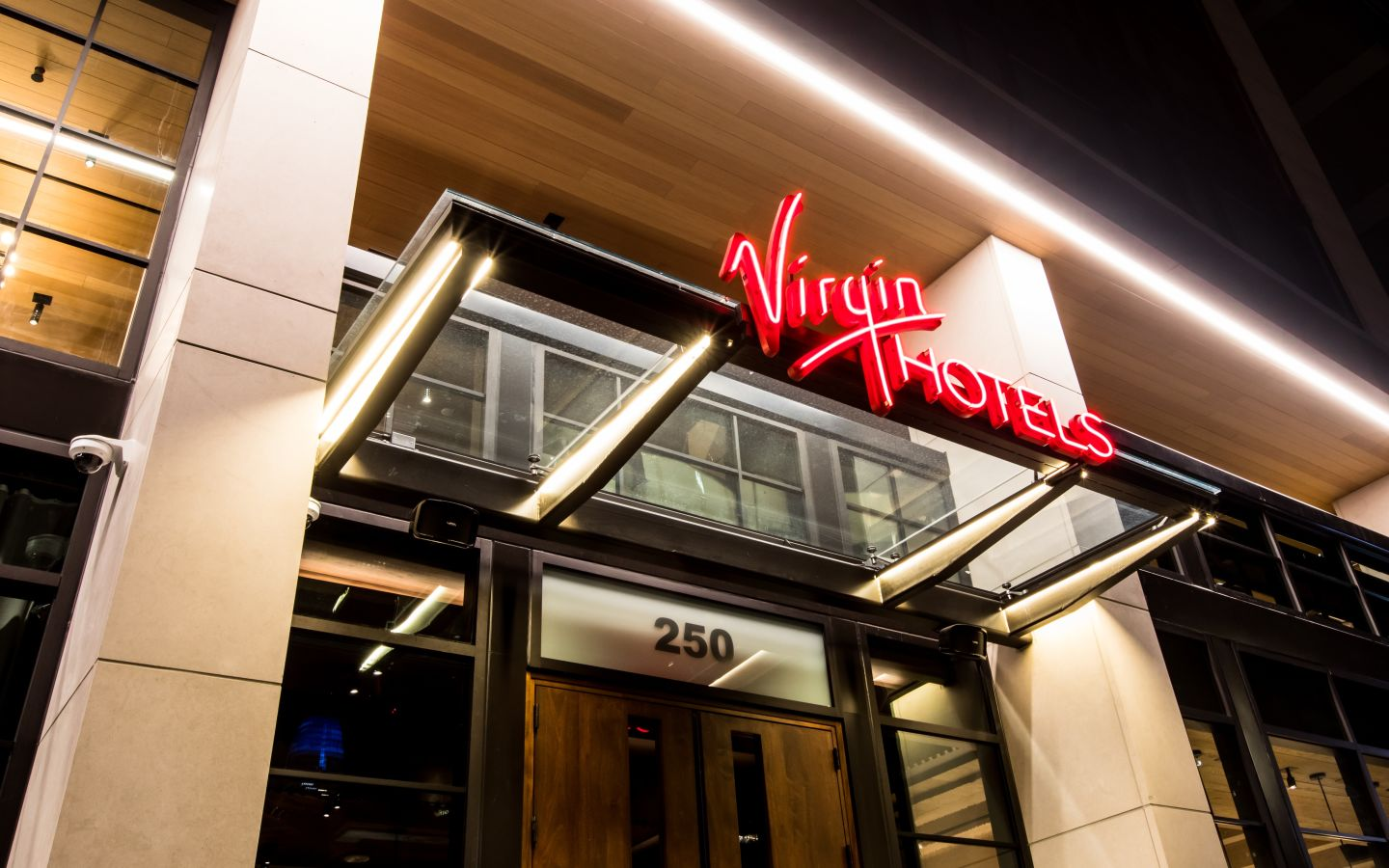 The exterior entrance to Virgin Hotels. The sign is lit up in red.
