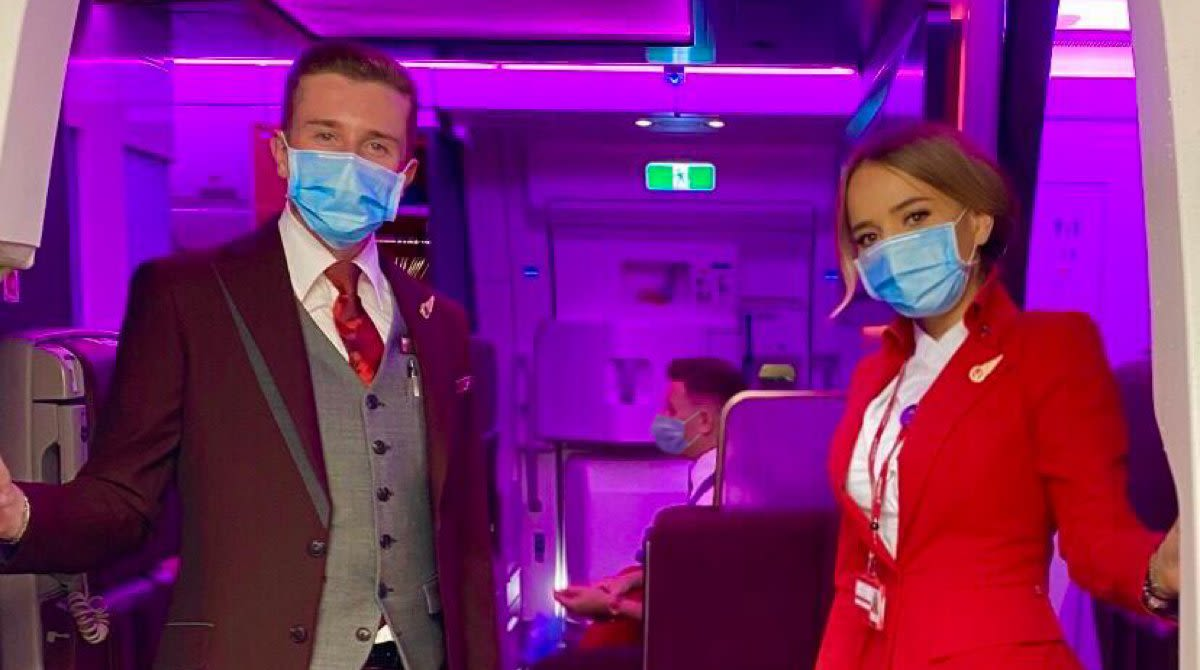 Two Virgin Atlantic cabin crew wearing face masks at the door of an aircraft