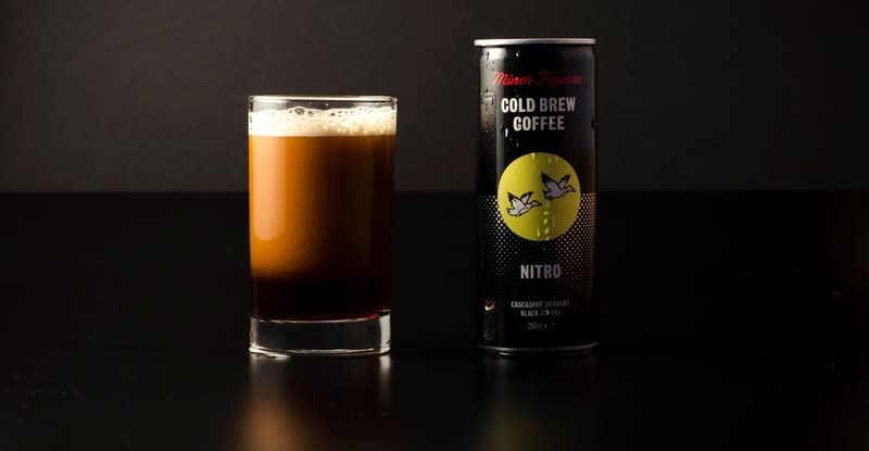 A glass with cold brew coffee in, next to a can of Minor Figures cold brew coffee