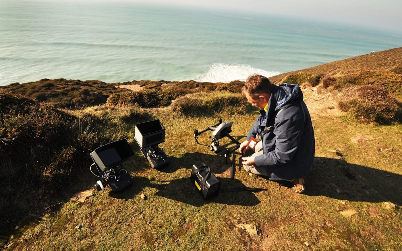 Adrian McDowell crouched next to drones on top of a cliff with sea views