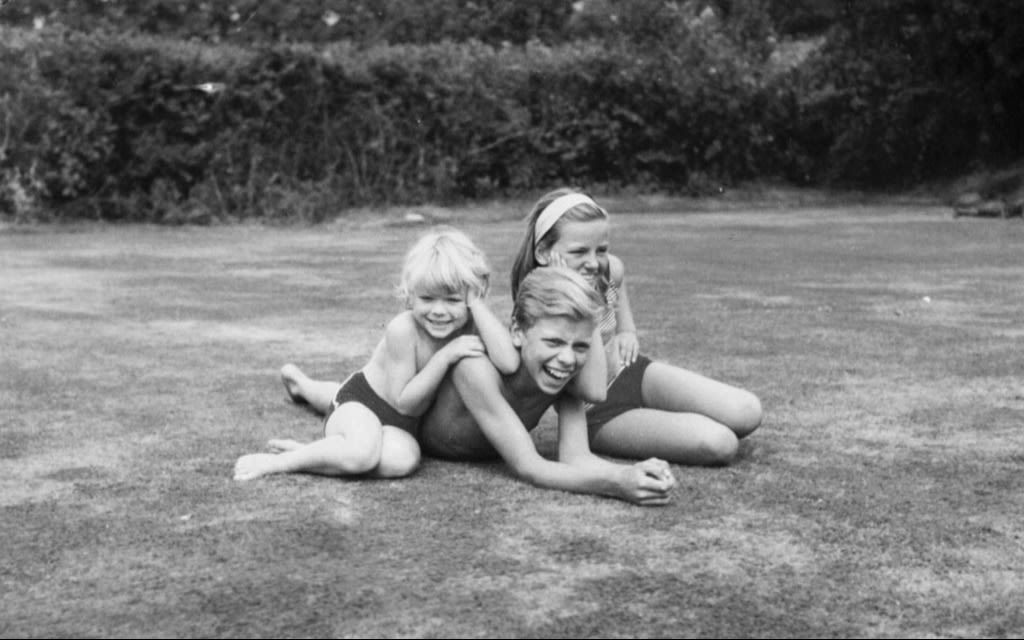 Richard Branson with his sisters lindy and Vanessa sitting on the grass as children