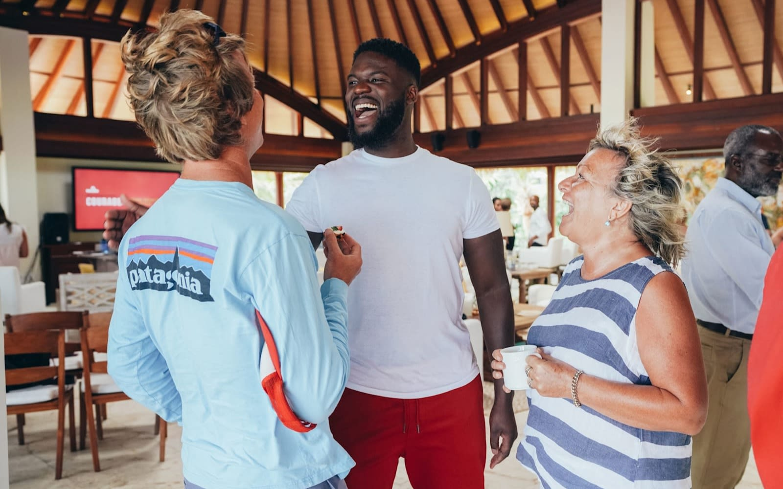 Karl Lokko speaking to man and woman at a Virgin Unite event on Necker Island