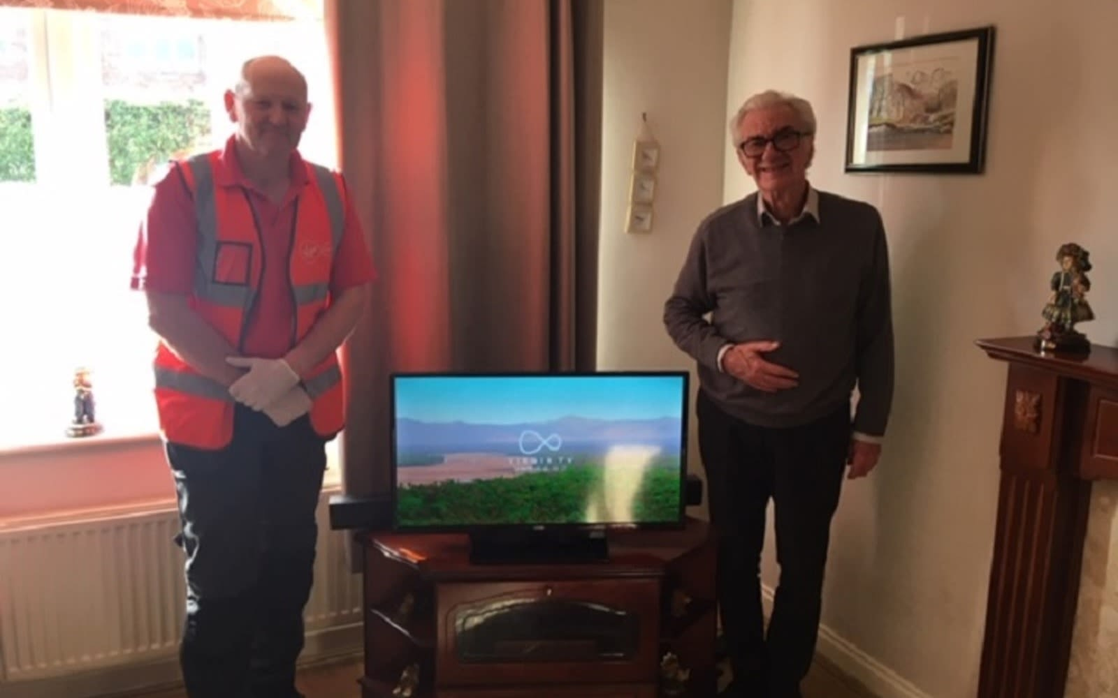Virgin Media Employee meets a customer standing next to a television