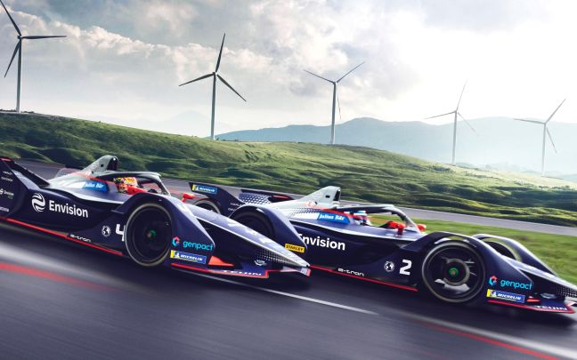 Two Envision Virgin Racing cars with wind turbines in the background