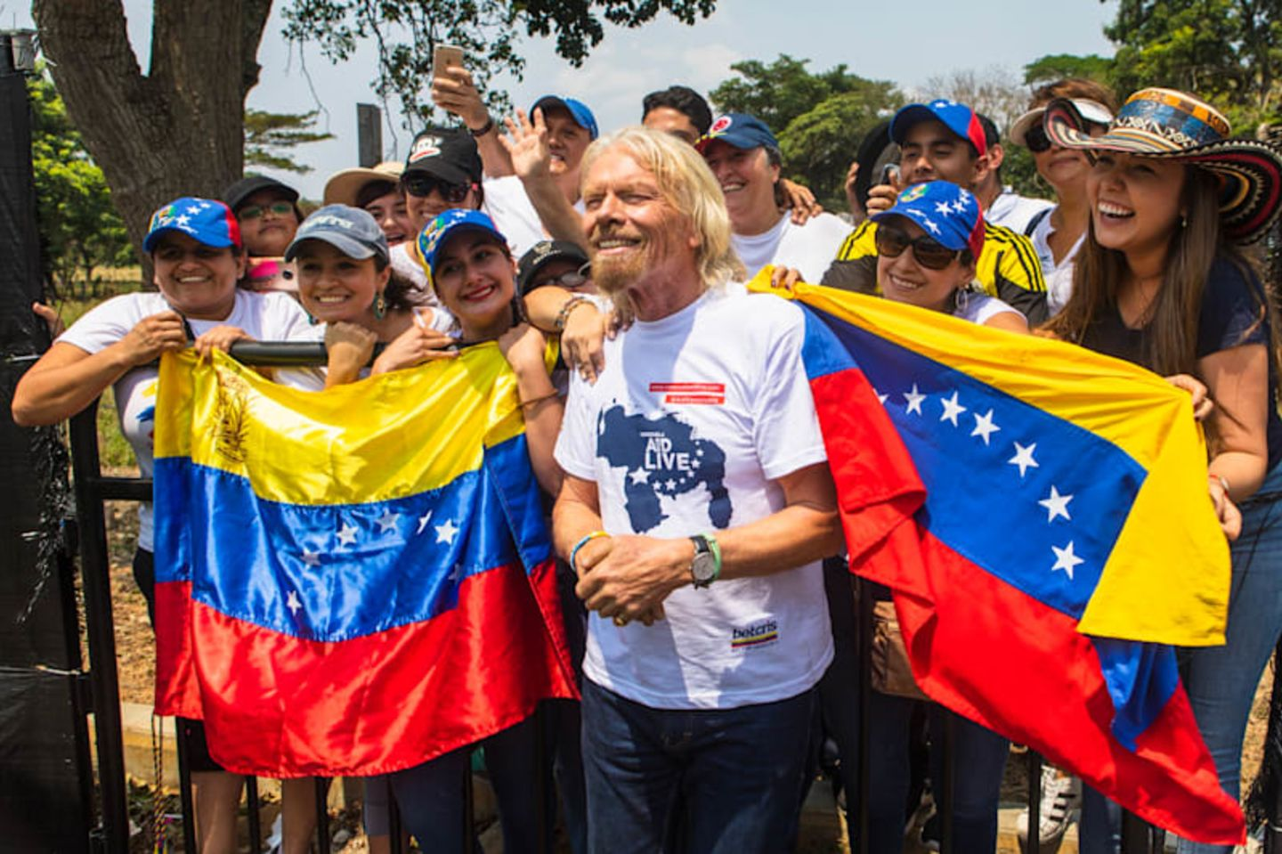 Richard Branson in front of a crowd of people holding the flag of Venezuela