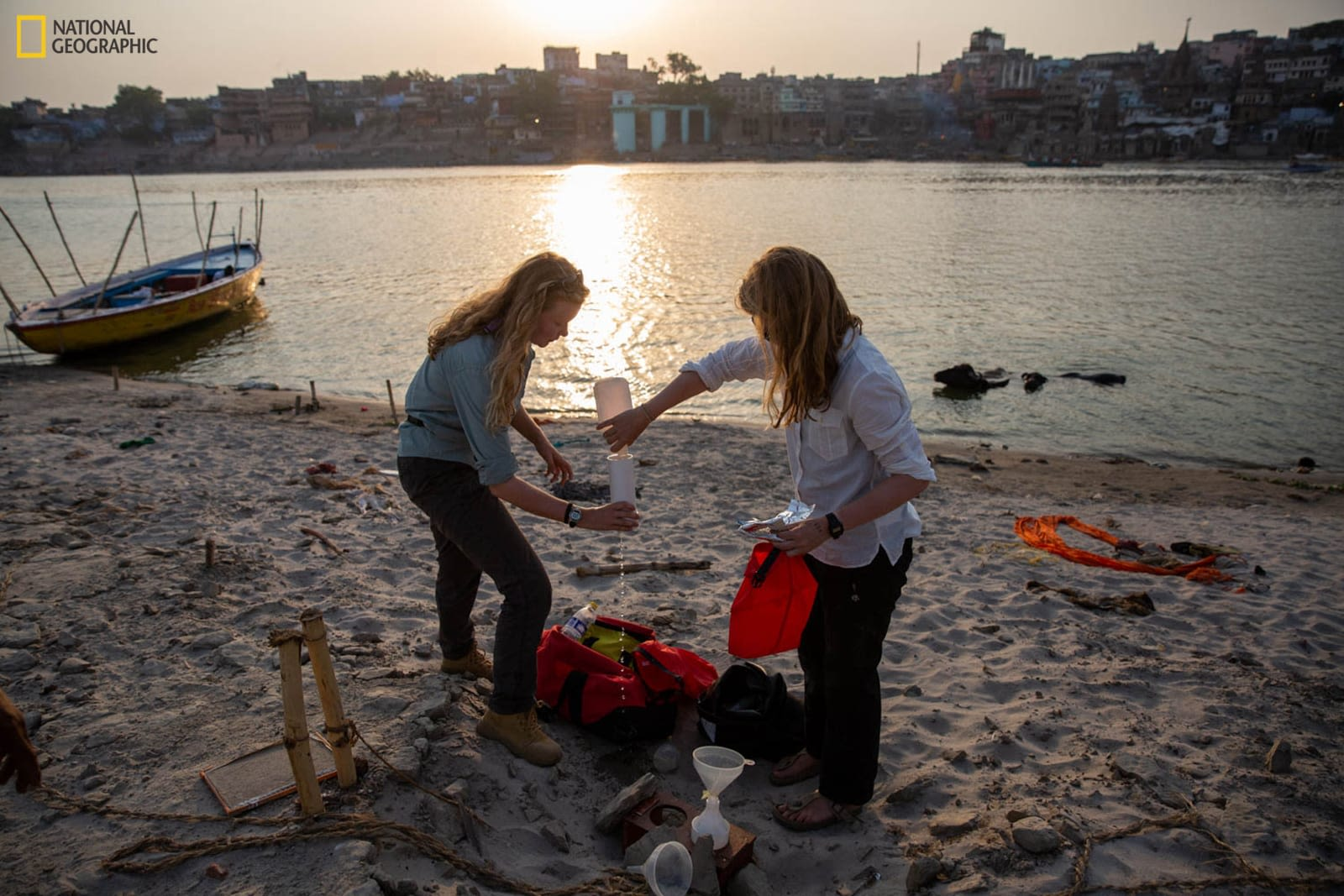 Two women cleaning up waste from sea