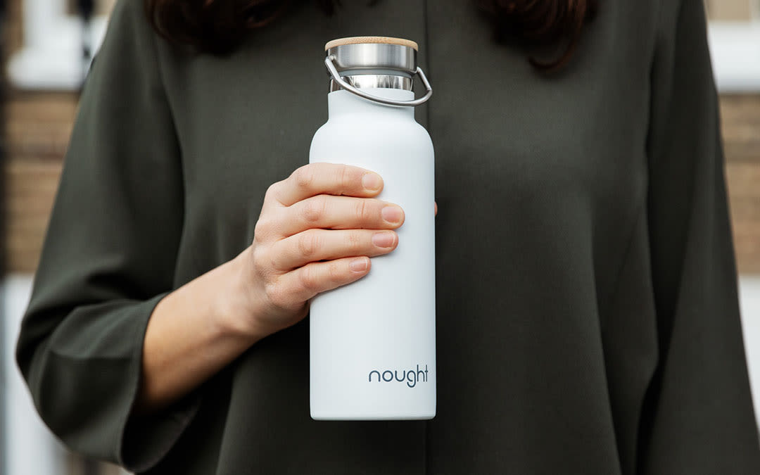 A woman holding a white metal bottle with the Nought logo on it