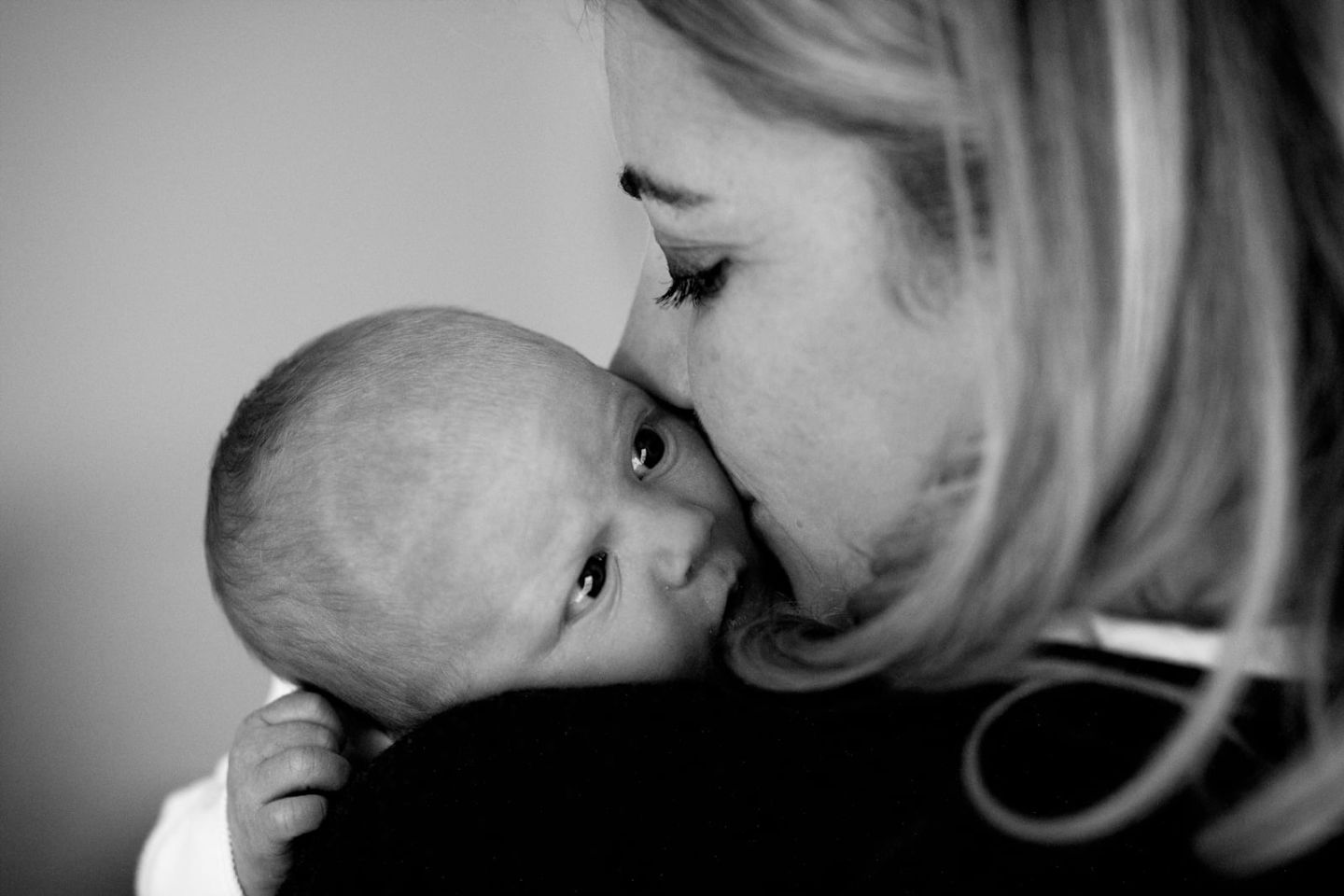 A black and white image of Holly Branson holding a newborn Lola to her shoulder