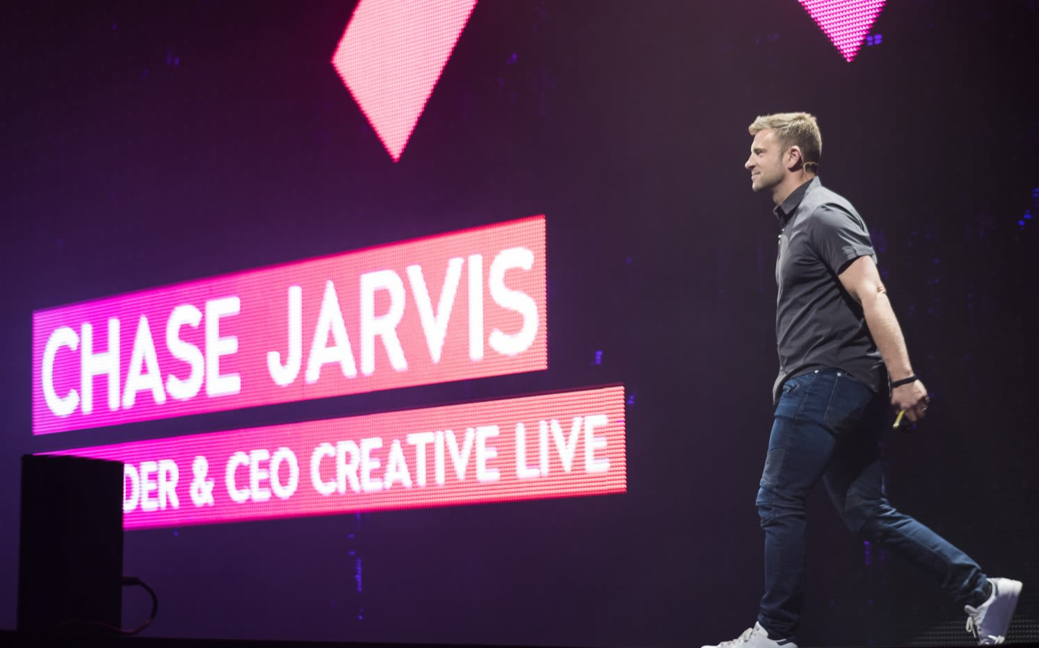 Chase Jarvis walking on stage with bright pink signs announcing his name and title
