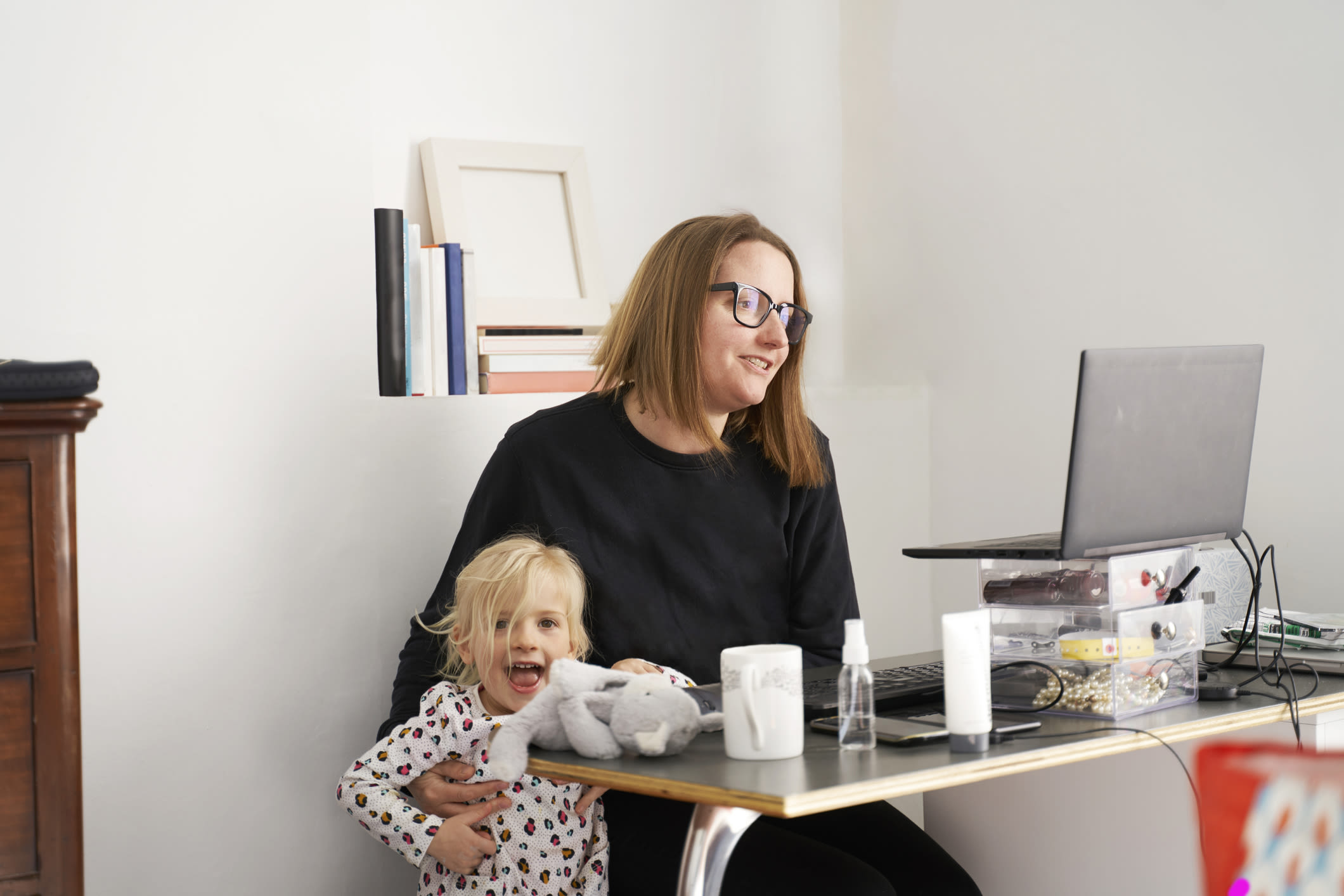 A woman working from home with a child