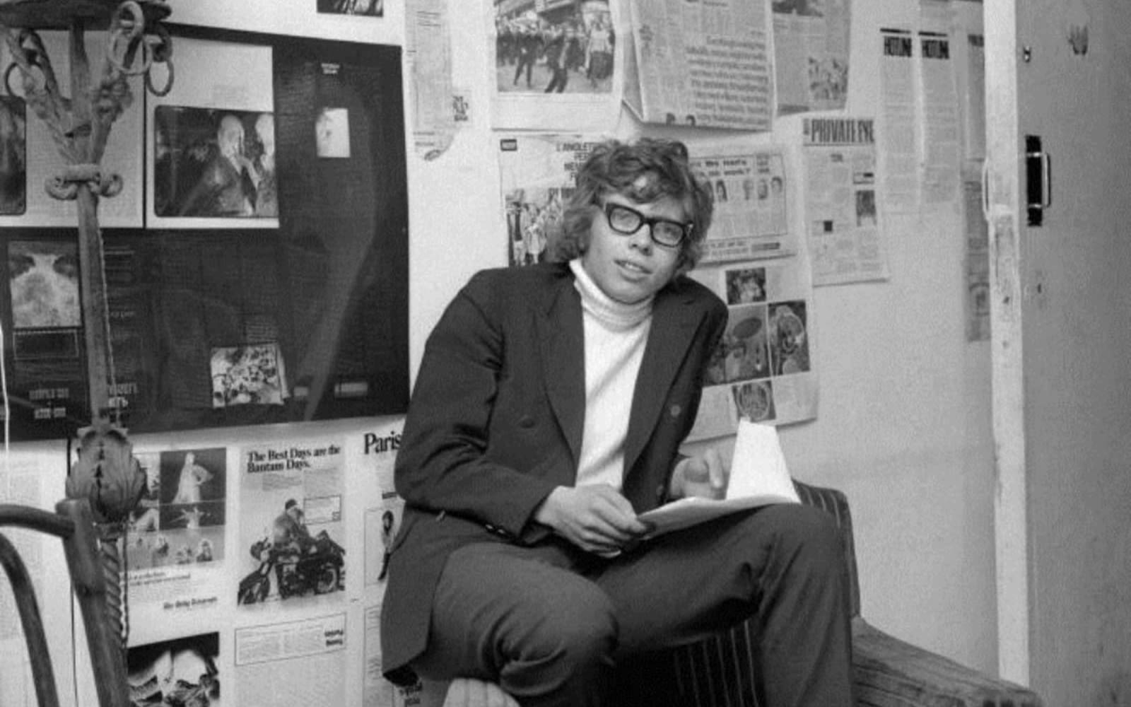 a young Richard Branson poses in front of newspaper clippings for Student Magazine