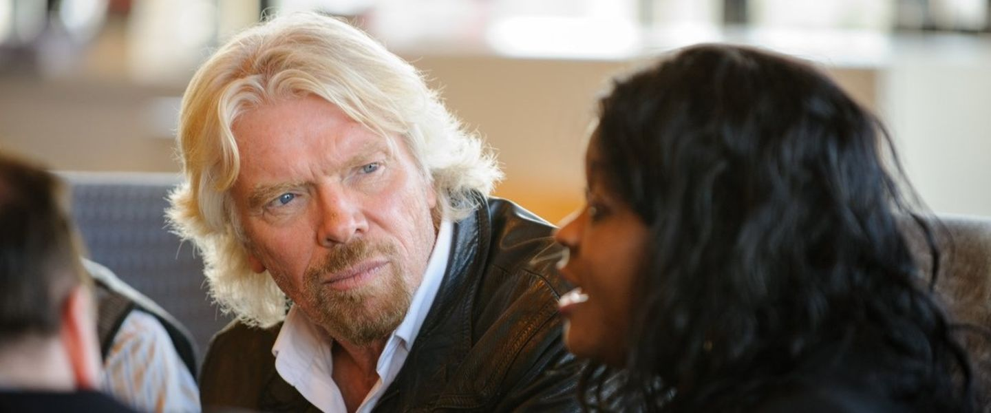 Richard Branson sitting next to a woman listening to her talking