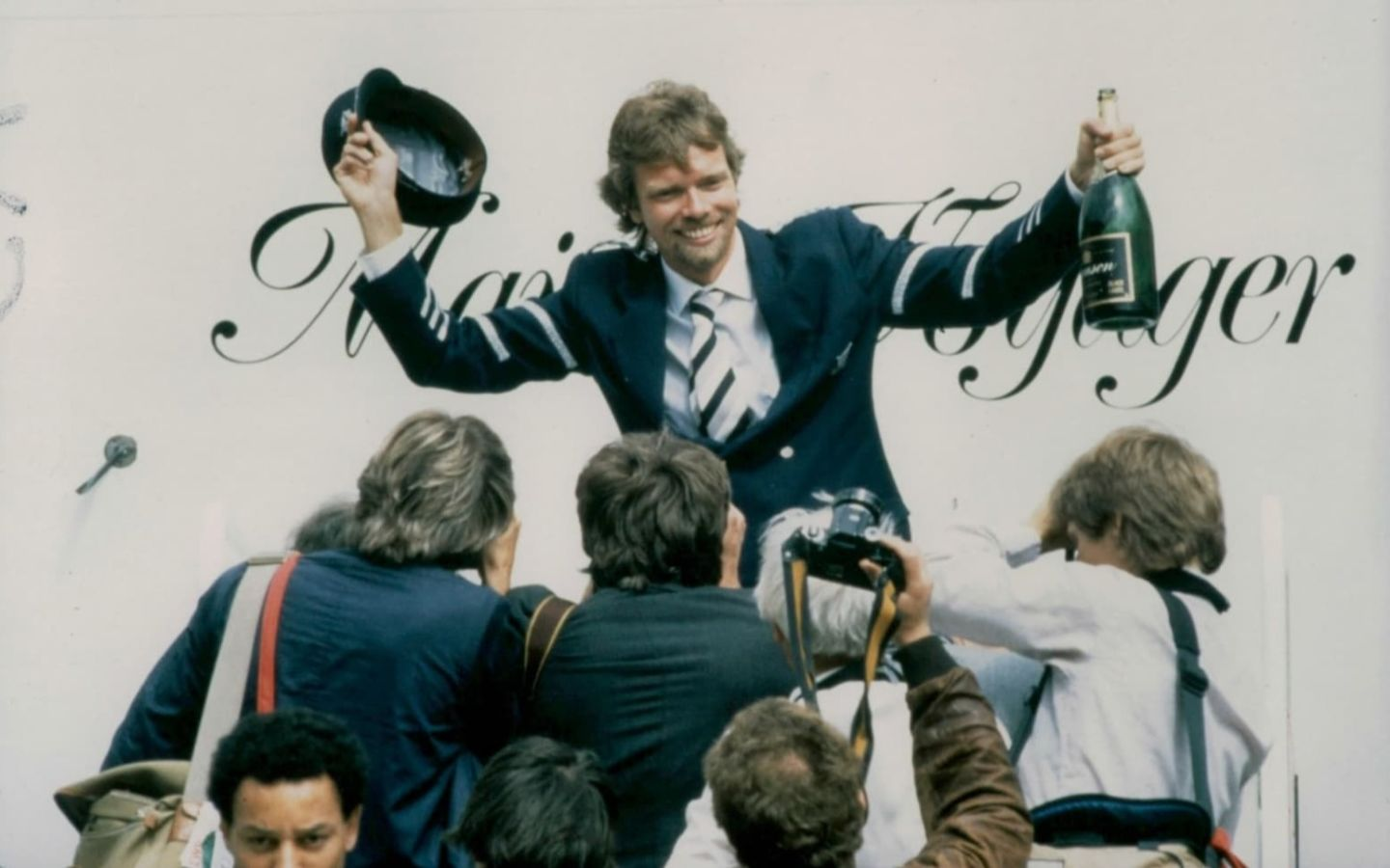 Richard Branson celebrates Virgin Atlantic's inaugural flight in 1984 with champagne in front of photographers