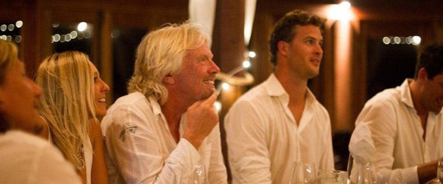Richard Branson sitting at a table with four others smiling and listening to someone speaking who is out of shot