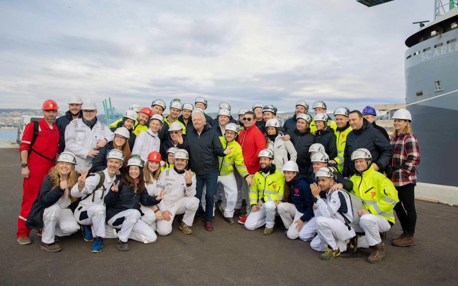 Richard Branson posing with Virgin Voyages' Scarlet Lady ship crew at the port