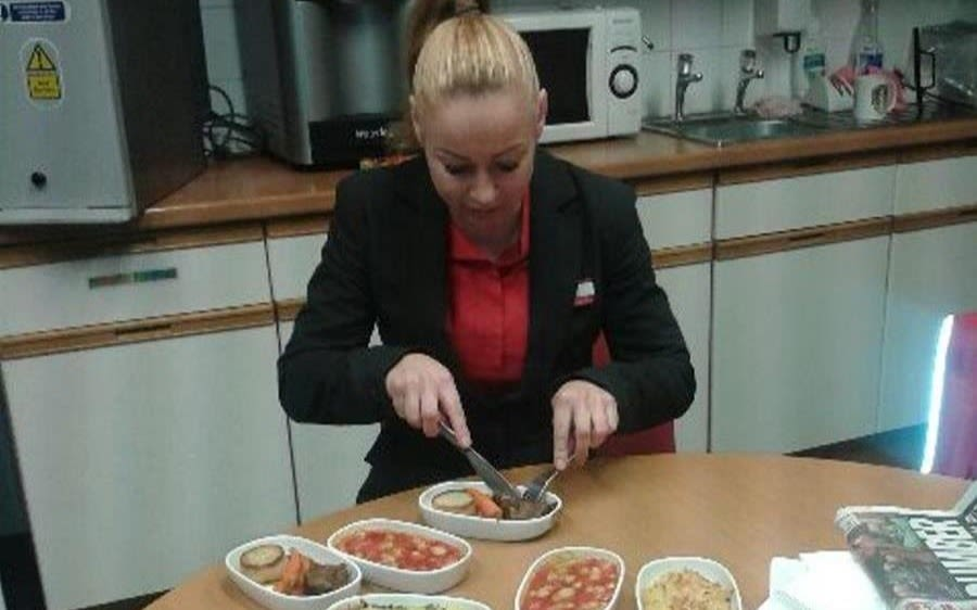 A woman in a Virgin Trains uniform sits at a kitchen table eating