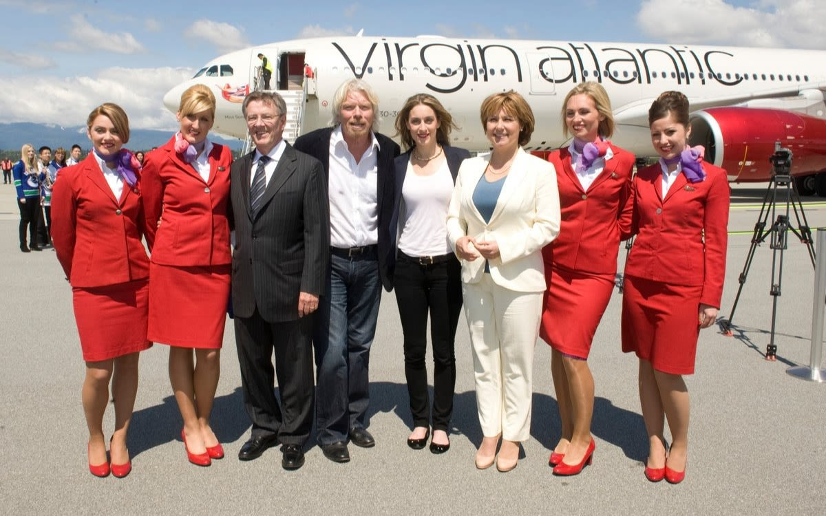 Richard Branson stands with Virgin Atlantic cabin crew in front of a plane