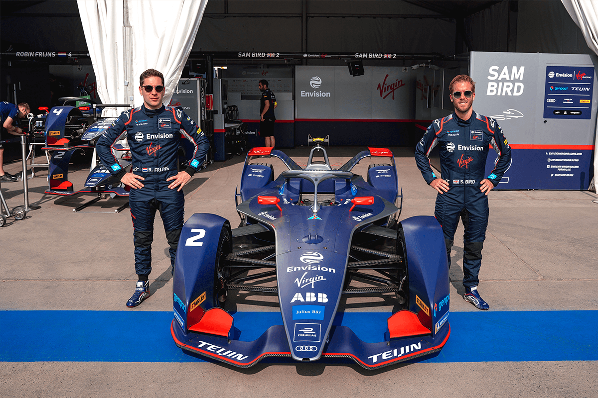 Envision Virgin Racing drivers Robin Frijns and Sam Bird stand next to an Envision Virgin Racing car