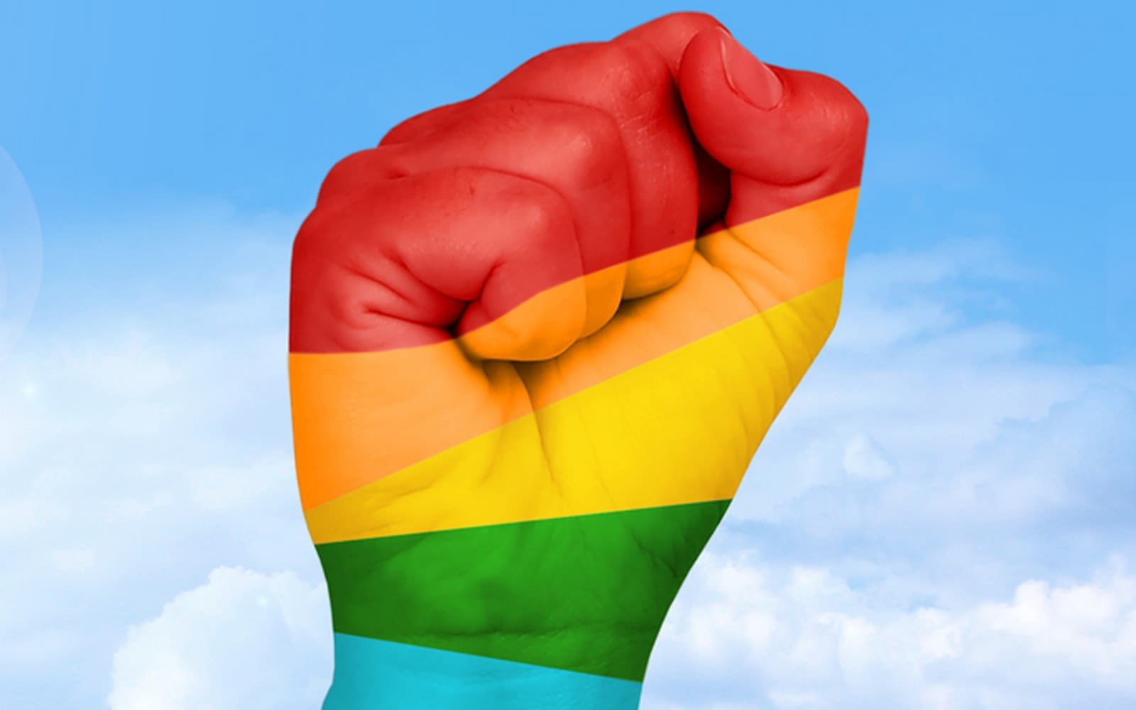 A clenched fist raised up with five colours of the rainbow in stripes across it - red, orange, yellow, green, blue