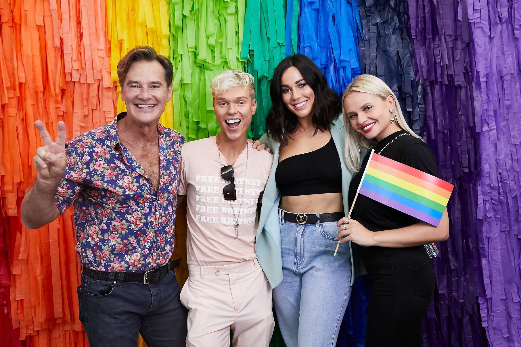Richard Reid, Jack Vigden, Sophie Cachia and Alli simpson stand in front of a rainbow backdrop