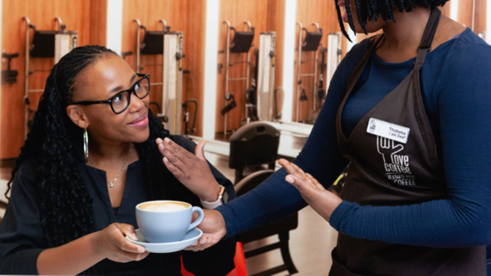A woman signs 'thank you' to a barista with hearing impairment at the in-office coffee bar at Virgin Active South Africa's national head office as she receives her drink