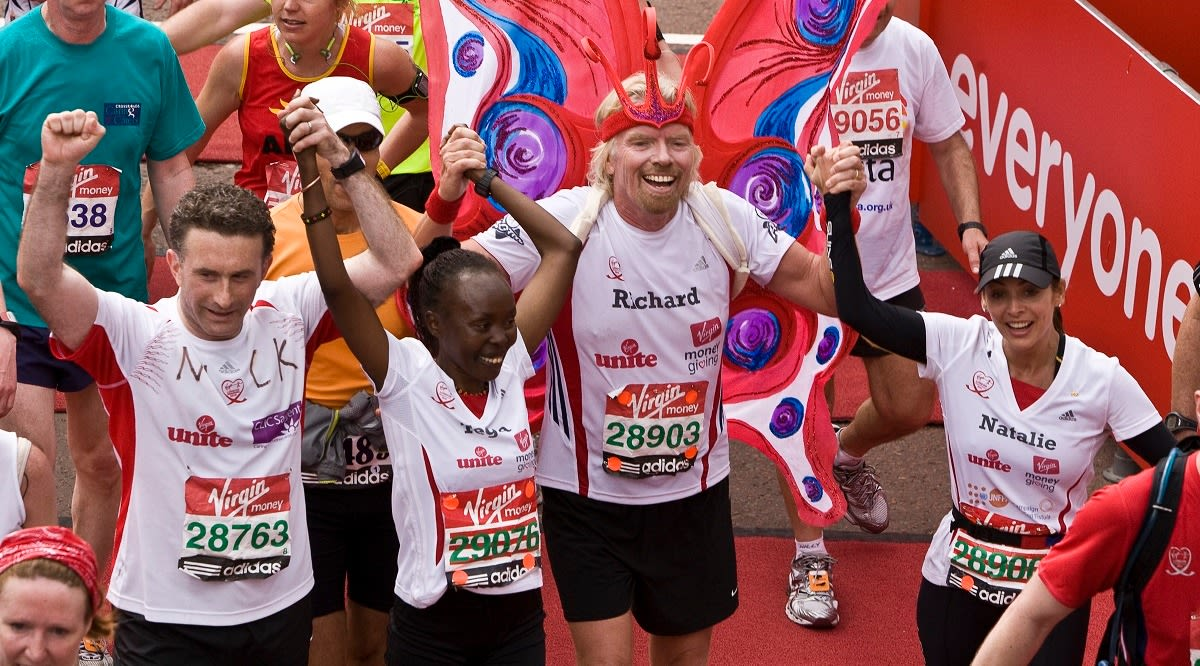 Richard Branson celebrates crossing the finishing line of the Virgin London Marathon