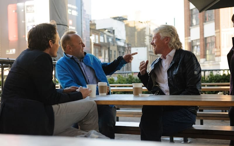 Richard Branson sitting at a picnic table talking and smiling with two men, one of whom is pointing at him