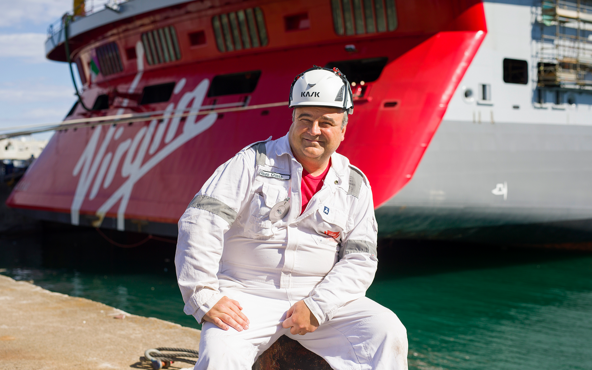 Virgin Voyages crew member - Mauro Chiesa - in front of the Scarlet Lady