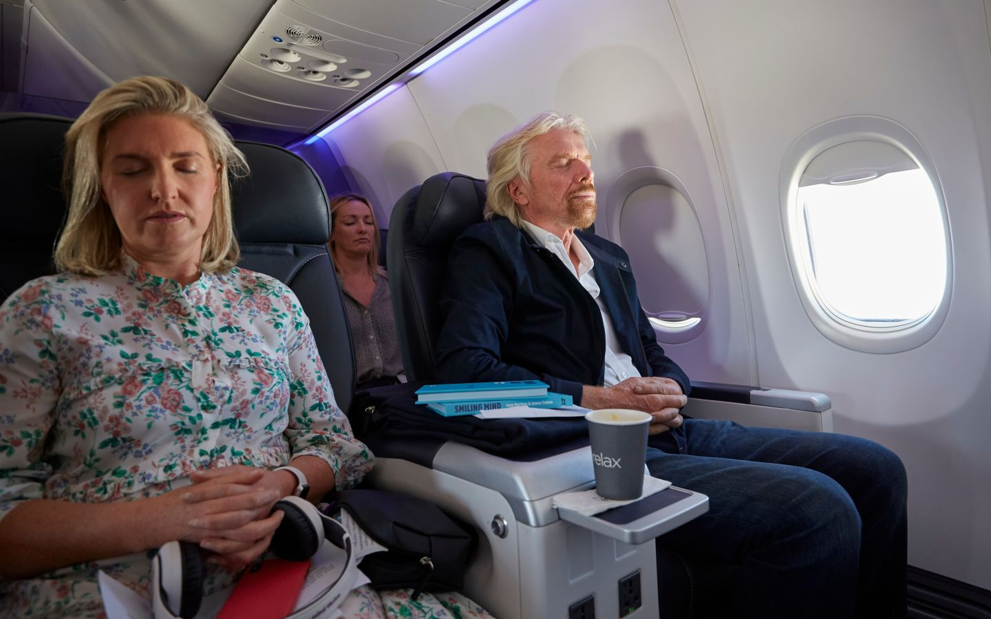 Richard Branson sitting on a plane, with his eyes shut, meditating. There is a women next to him and in the seat behind, also meditating.