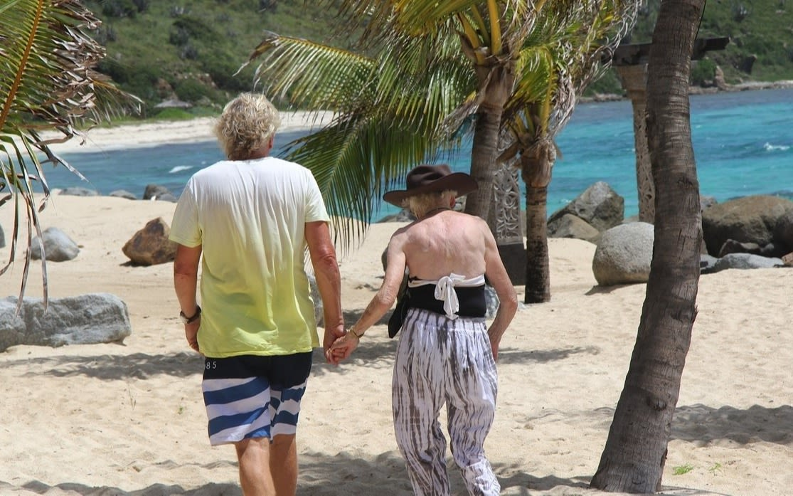Richard Branson and mum Eve walking on the beach on Necker Island