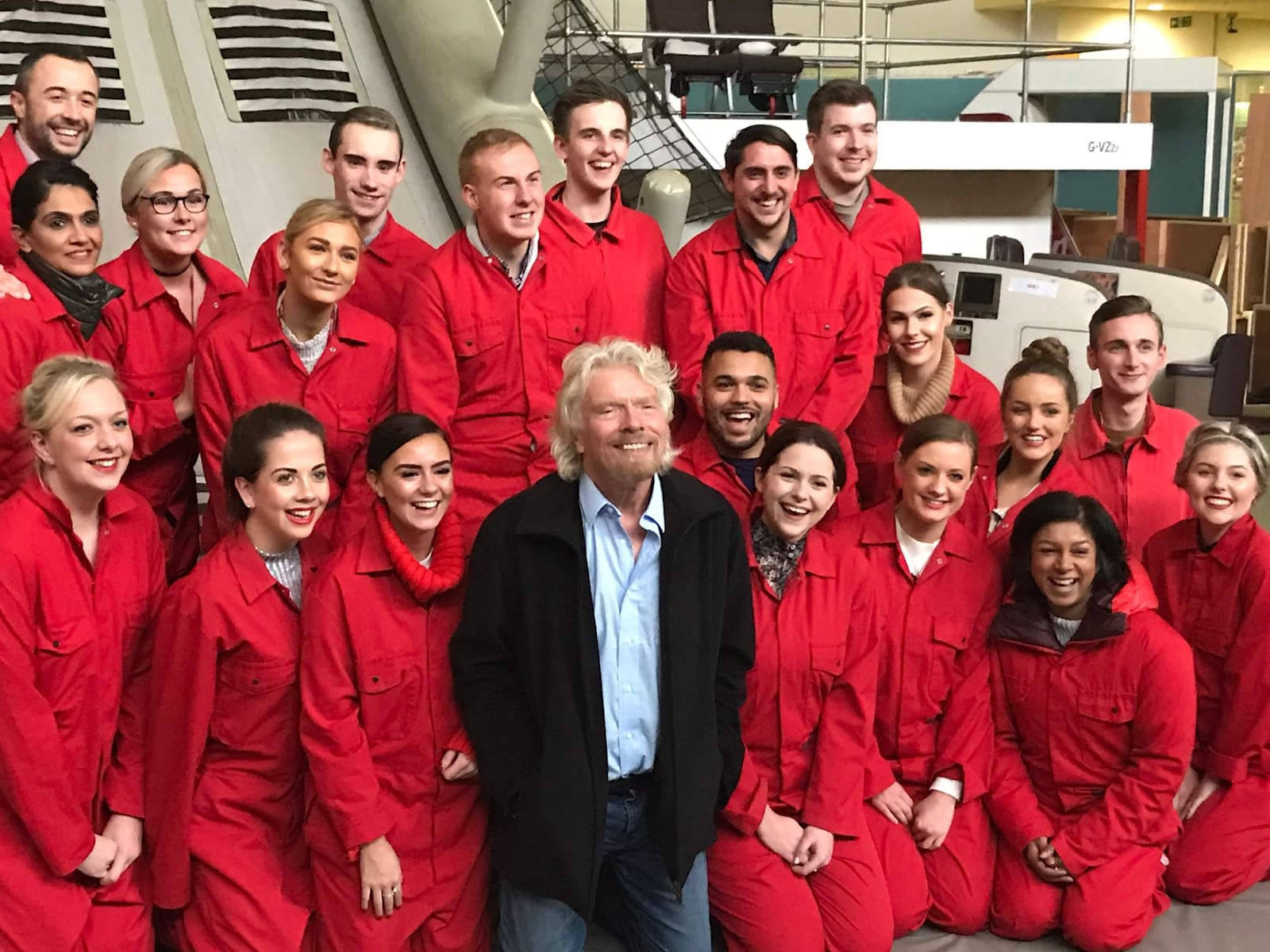 Richard Branson standing with cabin crew members after a safety drill. Cabin crew are wearing red jumpsuits. Everyone is facing the camera, smiling