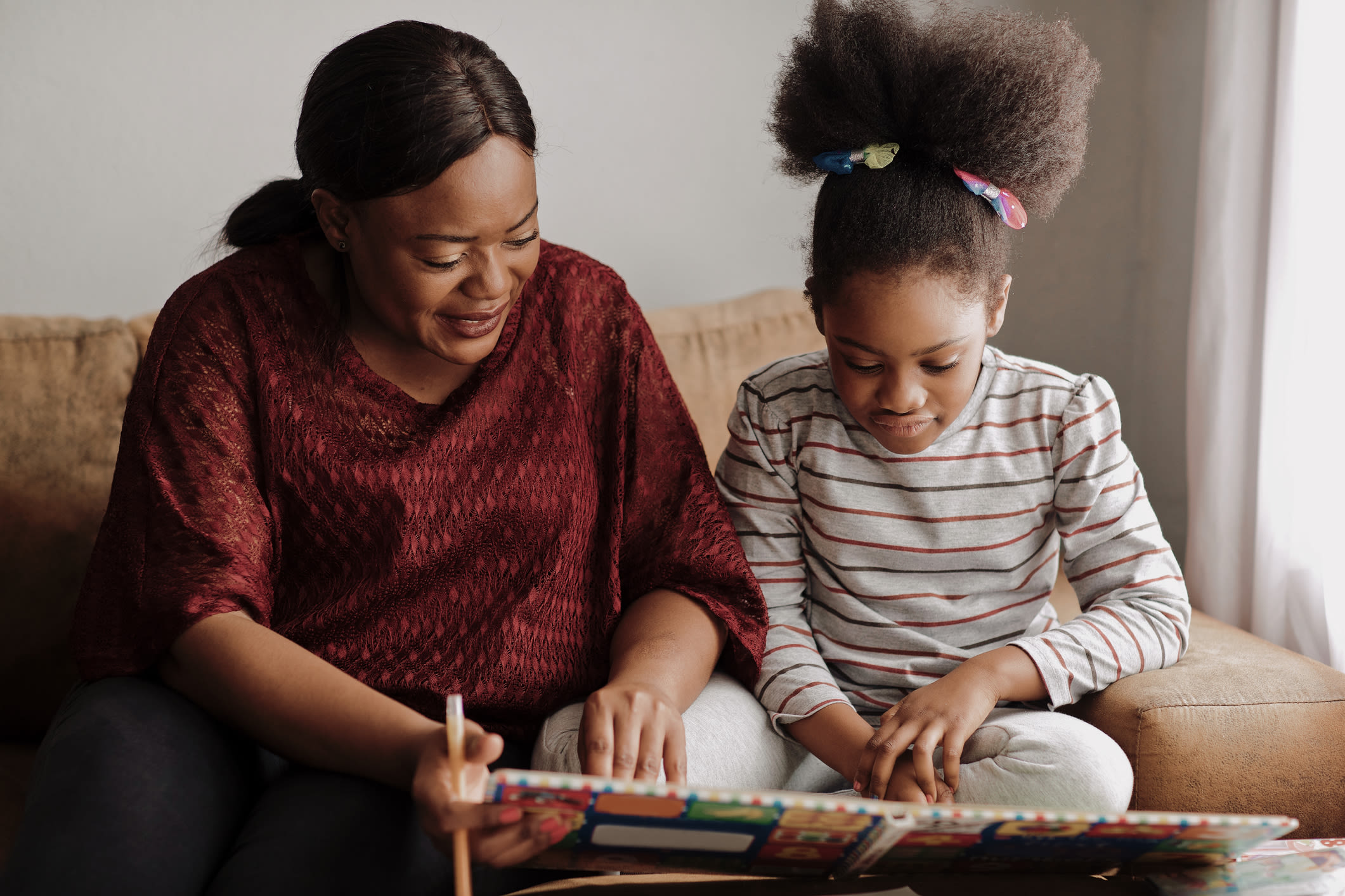 A woman and her daughter read together