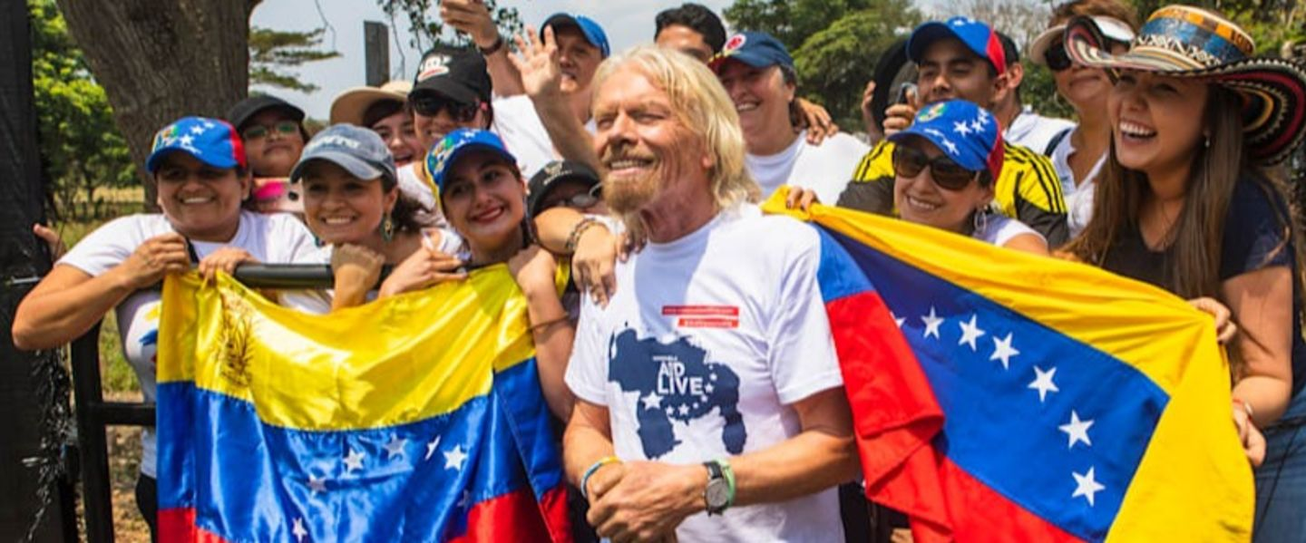 Richard Branson standing with a group of people holding Venezuelan flags