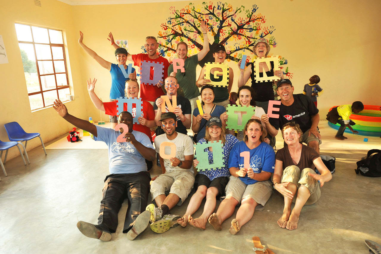 A group of people stand and sit in front of a tree mural on a yellow wall, each holding a letter or number to spell out 'Virgin Unite 2011'.