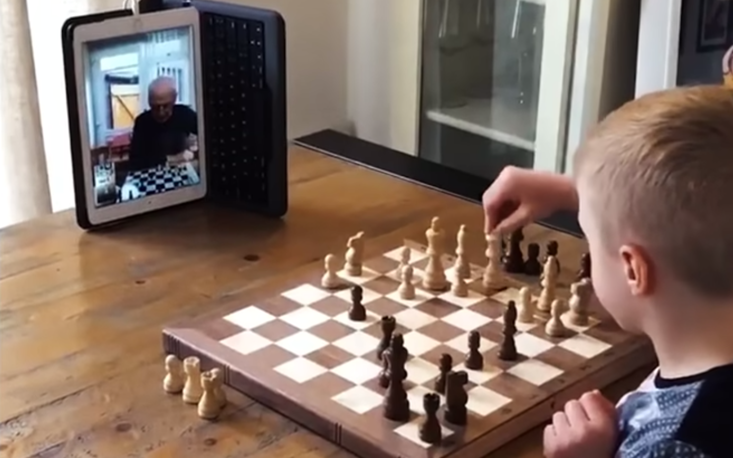 A young boy plays chess with his grandparent via video call on a tablet
