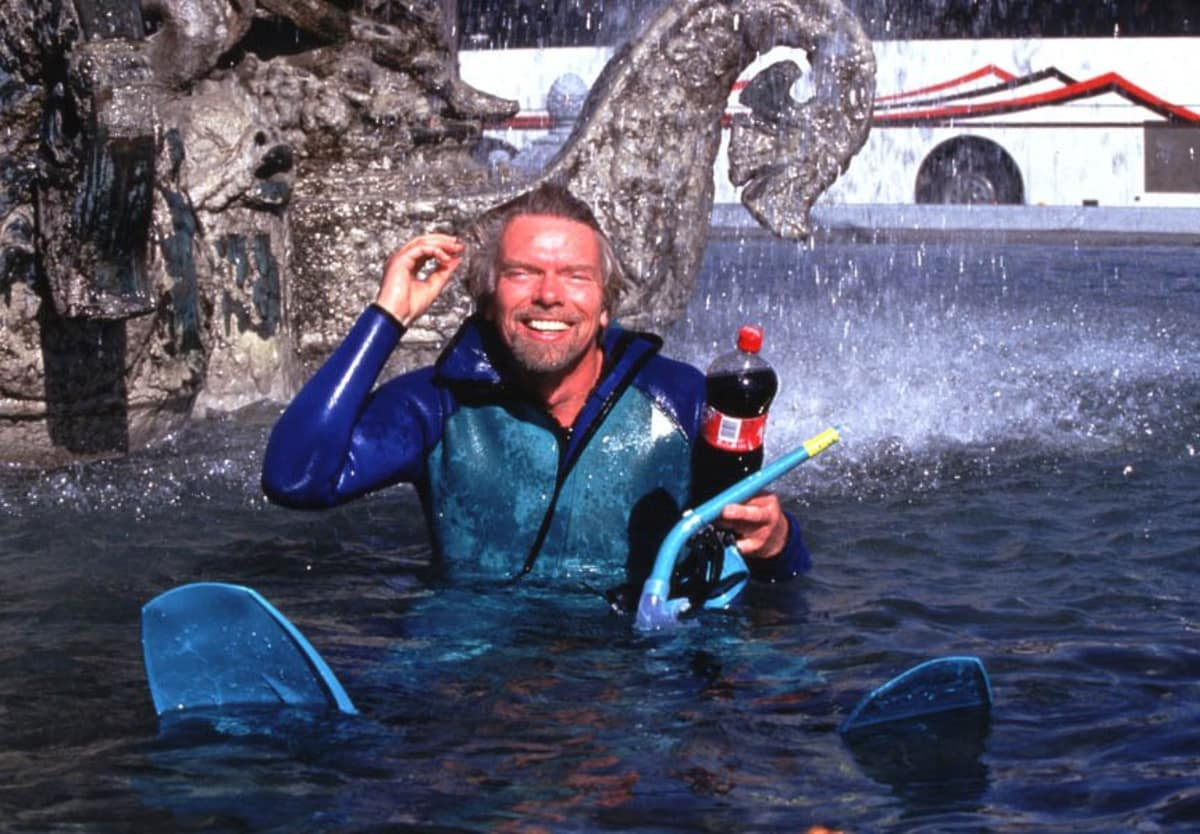 Richard Branson swims in a fountain with a Virgin Cola bottle