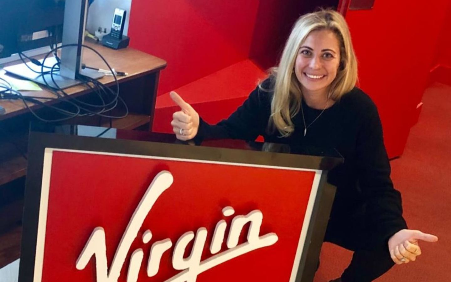 Holly Branson at the Virgin Management office in London - smiling in front of a Virgin logo
