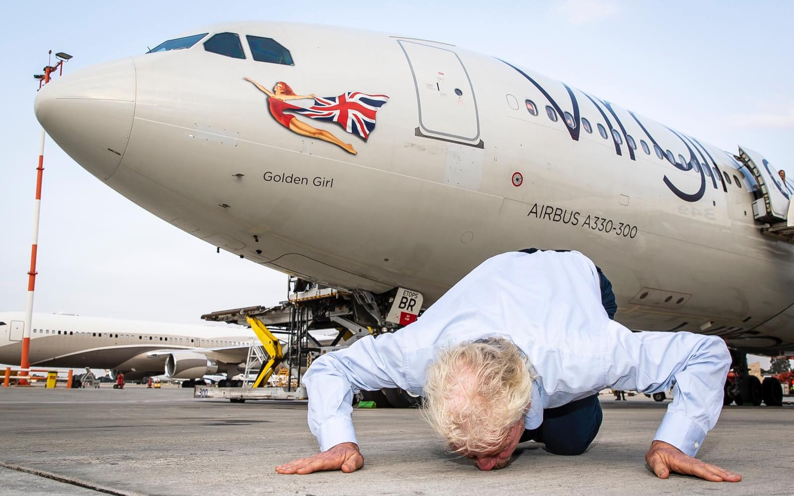 Richard Branson kisses the ground in front of a plane