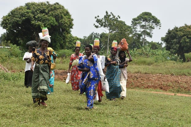 One Acre Fund | Farmers in Itanda, Uganda carry their planting supplies home