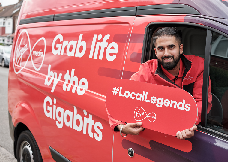 "A Virgin Media engineer leans out of the window of his van, holding a sign that reads ""#LocalLegends"""